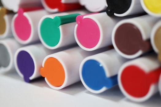 Pen markers multicolor caps macro closeup. Back to school composition. Colored market caps background.