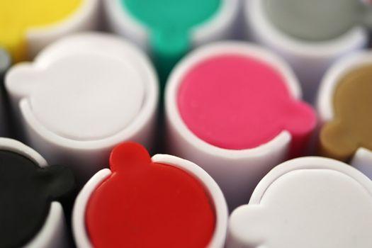 Colored market caps background. Pen markers multicolor caps macro closeup. Back to school composition.