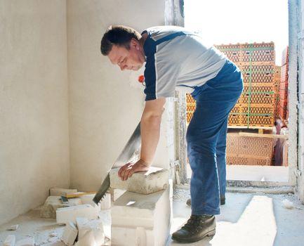 man worker saws silicate brick