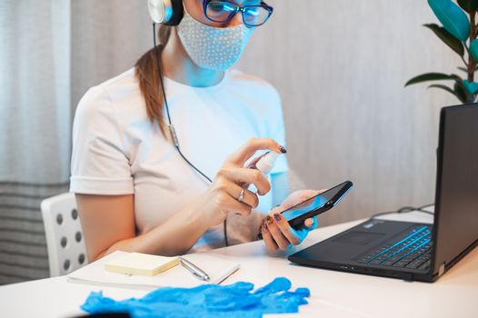 Woman disinfects the surface of the phone by sanitizer spray on the working place.