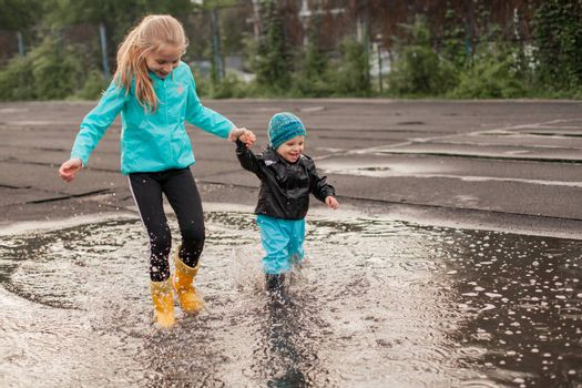 Boy and girl jumping in puddle in waterproof coat and rubber boots