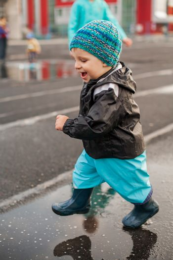 Happy boy jumping in puddle in waterproof coat and rubber boots