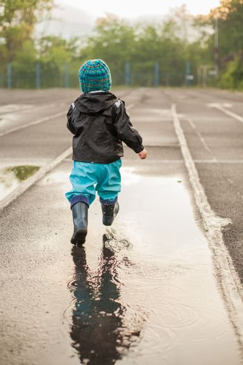 Child jumping in puddle in waterproof coat and rubber boots