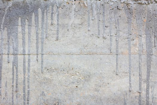 concrete wall with cement drips and copyspace in the middle.