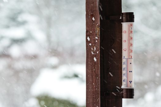 Concept image of winter coming - thermometer outside the house indicates below zero and it is snowing heavily.