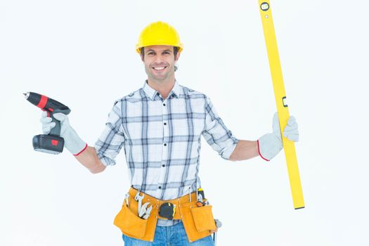 Technician holding portable drill and spirit level