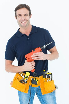 Confident carpenter holding portable drill machine