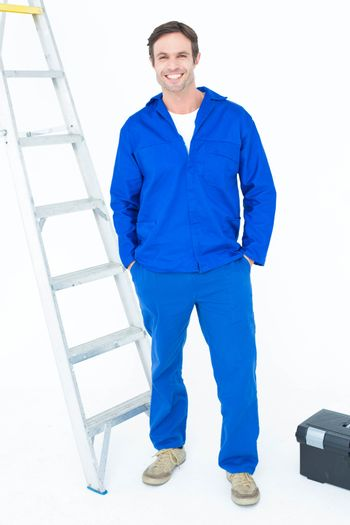 Carpenter in overalls standing with hands in pockets