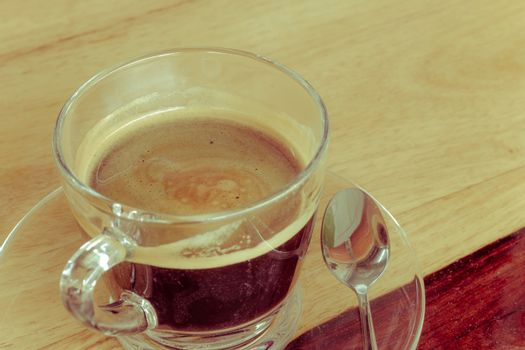Black expresso coffee in small glass cup on wooden table with te