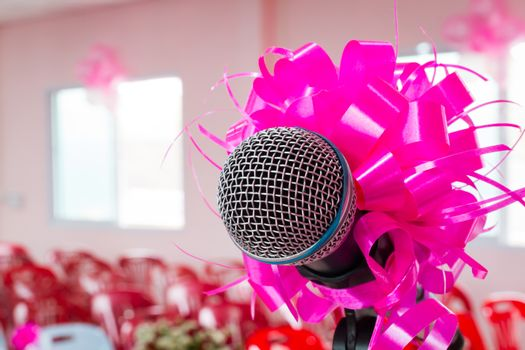 microphone with pink bow and ribbon in wedding ceremony hall
