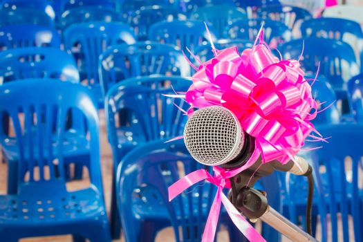 microphone with pink bow and ribbon in the background of blue chairs