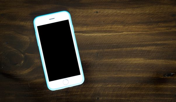 Smart phone on the table top of wooden background, dard tone.