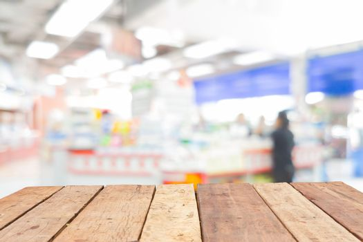 Wooden board empty table in front of blurred convenience store c