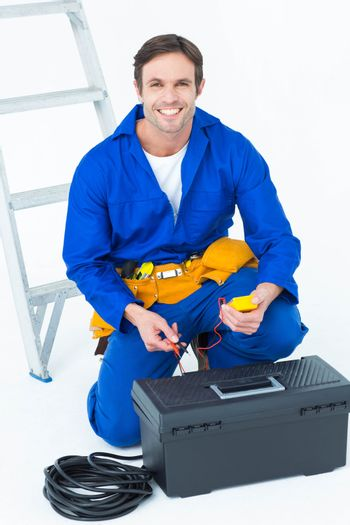 Happy electrician holding multimeter
