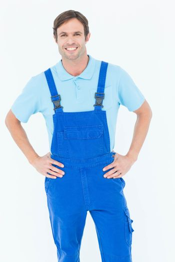 Happy carpenter in overalls with hands on hip
