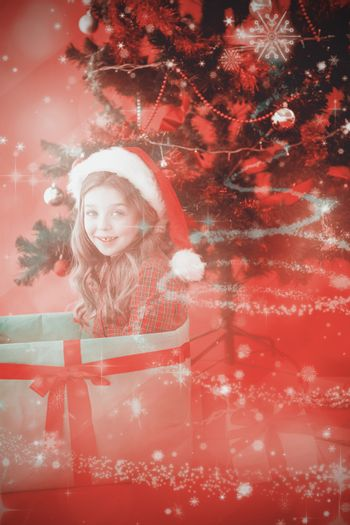 Festive little girl sitting in large gift against glittering christmas tree design