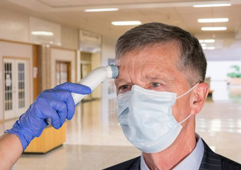 Mockup of hospital, clinic or shopping mall with senior adult wearing mask having a fever or temperature test taken to check coronavirus status