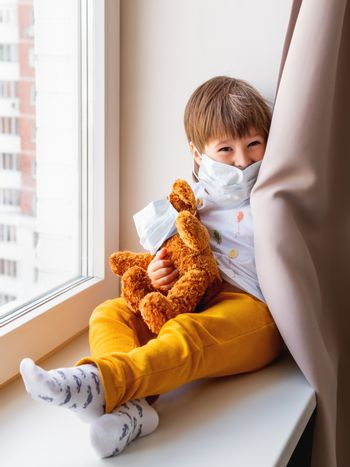 Toddler boy sits with teddy bear in medical masks. Kid with plush toy plays hide-and-seek behind curtains. Browh plush bear and child on home quarantine because of coronavirus COVID-19.