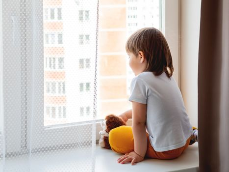 Toddler boy sits with fluffy hedgehog. Kid with plush toy look through window outside. Child on home quarantine because of coronavirus COVID-19 waiting for somebody.