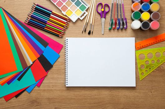 set of school supplies with pencil, colored pen, watercolor paint, notebook and scissors