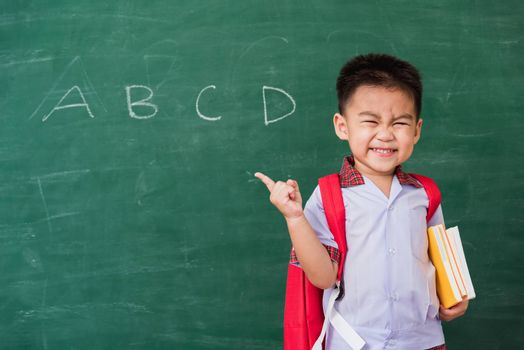 Back to School. Happy Asian funny cute little child boy kindergarten in student uniform and school bag and books smile point finger space side away on school blackboard, First time to school education