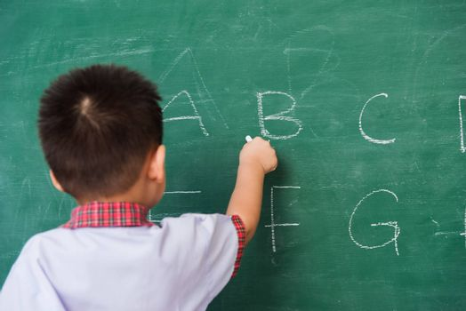 Back to School. Happy Asian funny back of cute little child boy kindergarten preschool in student uniform writing ABC with white chalk on green school blackboard, First time to school education