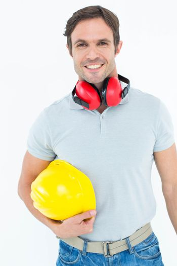 Happy carpenter with hard hat and ear protectors