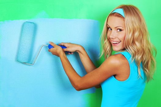 Happy woman paints her appartment walls from green to blue using paint roller , copy space for text