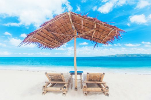 Beach chairs and umbrella made of straw and bamboo at beautiful tropical sea beach