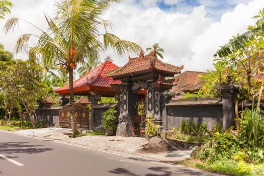 House with figured gate and tiled roof in Ubud, Indonesia. Traditional asian architecture.