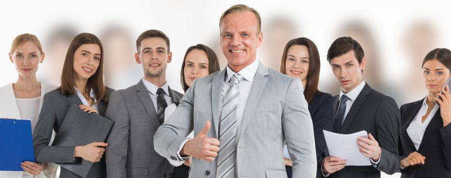 Business man hold hand with thumb up gesture, business man excited happy smile over group of businesspeople team background