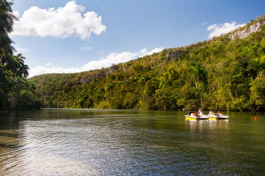 Tourists on catamarans float down the river between wooded mountains. Cuba.