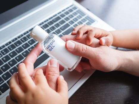 Self-isolation because of coronavirus outbreak. Man's hand with medical sanitizer gel for skin sterilization. Father is remote working with his little son.
