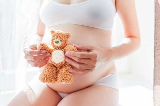 Pregnant woman in white underwear with toy bear. Young woman expecting a baby.