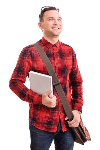 Portrait of a smiling young man in stylish plaid shirt with a shoulder bag holding a notebook, isolated on white background. Male student holding a book. Education concept.