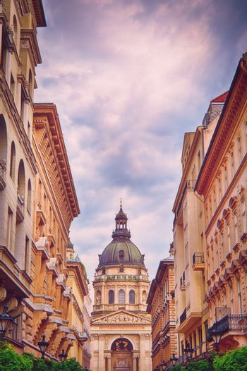 St. Stephen's Basilica in Budapest on a beautiful day seen from the tourist walking street through the buildings.