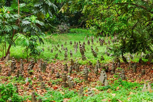 Graveyard with small monuments among grass. Cemetery in Singapore.