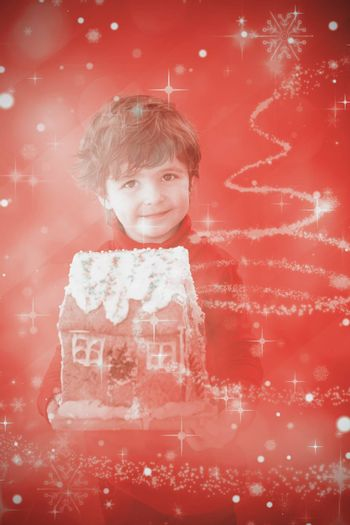 Festive little boy holding gingerbread house against glittering christmas tree design