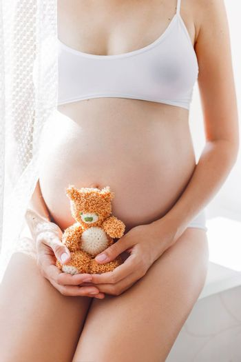 Pregnant woman in white underwear with knitted toy teddy bear. Young woman expecting a baby. Cozy happy background in sunny morning.