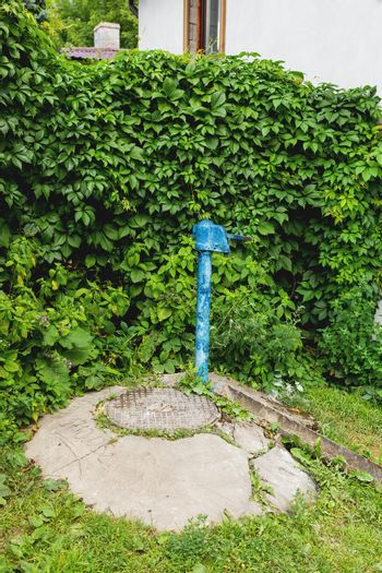 Metal sewerage hatchway and old fashioned water standpipe with bas relief. Iron manhole. Serpukhov, Russia.