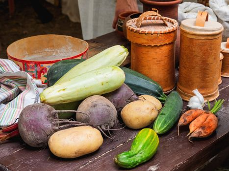 Fresh vegetables and vintage dinnerware, birchbark crockery and old fashioned household items on historical festival Times and Epochs. Moscow, Russia.