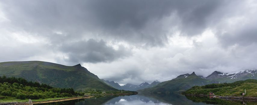 Beautiful scandinavian landscape with fjord, mountains and storm