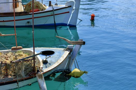 Fishing schooners with fishing nets on board are anchored in the clear waters of the Ionian Sea. Loutraki, Corinth, Greece.
