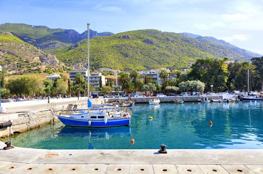 Old fishing schooners, boats and boats are moored at the pier of the Gulf of the Ionian Sea amid the sunlit embankment and mountain range.