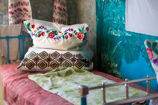 An ancient iron bed with embroidered cushions.Old Iron Bed with pillows.Embroidered pillows on an old bed
