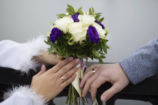 Bridal bouquet and hands with wedding rings. The bride's bouquet. Wedding rings.
