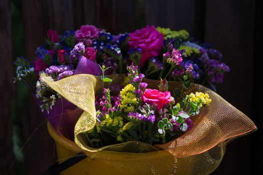 A bouquet of flowers in a plastic bucket. Buetnatural flowers