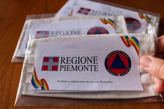 Turin, Piedmont, Italy. May 2020. Coronavirus. The region in collaboration with the civil protection, has delivered washable and reusable masks. Note the two logos