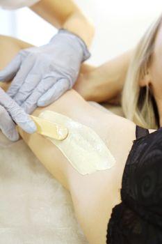Waxing woman armpit with spatula. Salon wax beautician epilation procedure