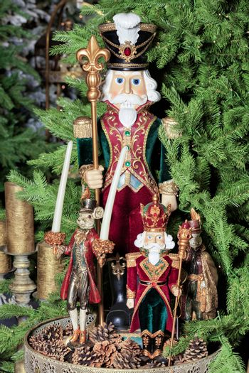 Christmas - New Year's toys and ceramic figures of fairy-tale characters on a background of green spruce branches and cones.